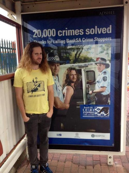 funny criminal stands in front of criminal poster