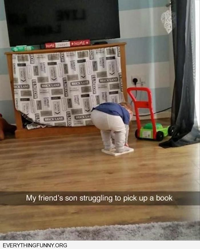 funny little boy tries to pick up book while standing on it