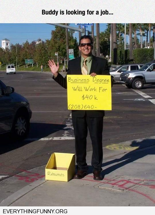 funny creative out of work executive stands on corner with sign that says business degree in business suit with resumes
