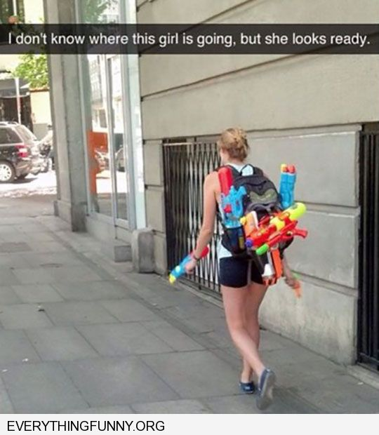 funny girl loaded with water guns i don't know where she's going but she looks ready