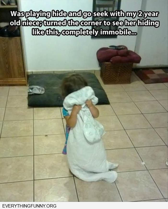 funny 2 year old hides behind her blanket standing in the middle of room thinking she can't be seen