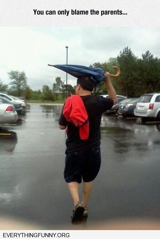 funny caption you can only blame the parents kid puts closed umbrella over his head to keep dry