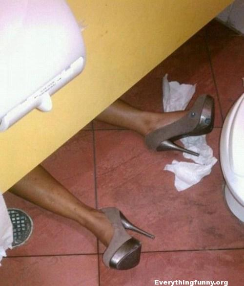 funny photo woman with heels passed out in toilet stall public bathroom
