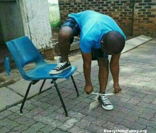 funny photo man puts one foot on chair but bends down to tie laces on shoe on the ground
