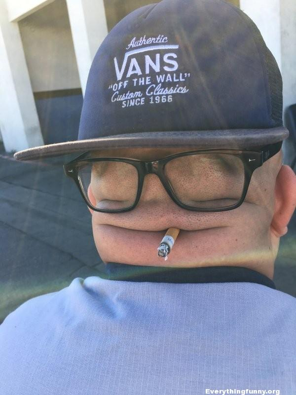 funny photo man puts cigarette glasses and baseball hat on bald head